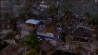 One year anniversary of Typhoon Haiyan marked / protests for more help for survivors LIB AIR VIEW AERIAL over devastated buildings in town of Cebu