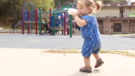 A one year old baby girl learning to walk outdoors in a park on a sunny day.