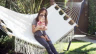 One year old baby, his mom and dog outside in hammock