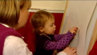 One year old girl has ground breaking surgery using calf's jugular vein Megan Mills drawing on board and eating biscuit