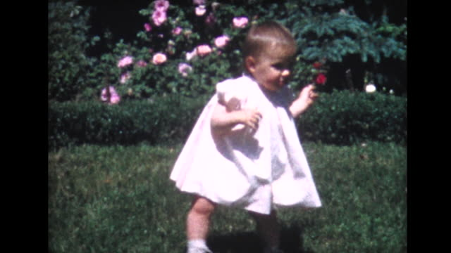 1958 one year old girl takes faltering steps in garden