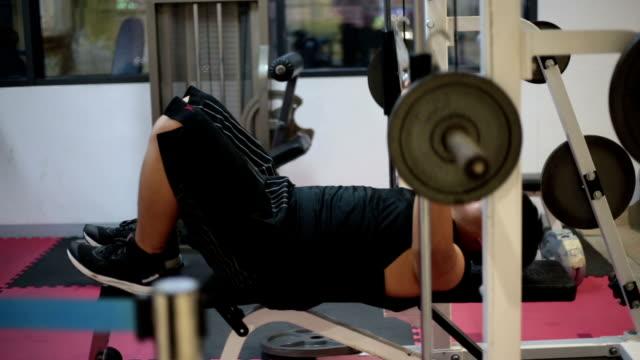 Een jonge man met een overgewicht in de sportschool doen een borstpres oefenen met barbell.