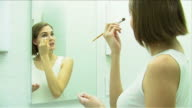 One young woman is making up using eye shadow