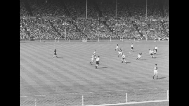 Ongoing soccer game between Manchester City and Birmingham City in final of FA Cup at Wembley Stadium crowd in stands in bg / LS stadium field and...