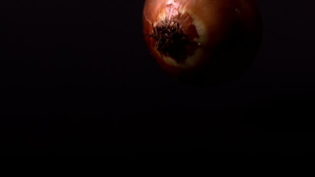 Onion falling against black background