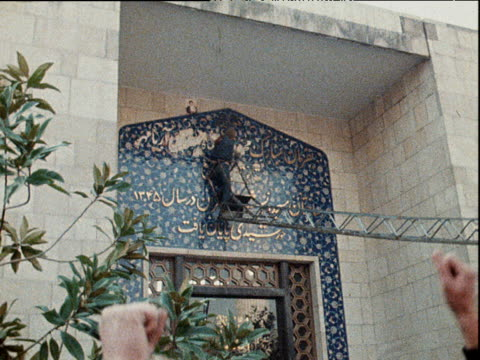 Onlookers cheer as name of Shah Mohammad Reza Pahlavi of Iran is hacked of facade of Tehran University mosque power struggle in wake of Shah's...