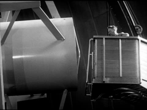 Open elevator lifting unidentified astronomer scientist up walking into cylinder BEHIND Astronomer setting up photographic plate adjustable diaphram...