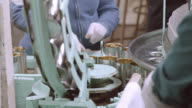 ECU of open olive cans dropping from conveyor into filling wheel at vintage olive processing plant / Ontario, California, USA