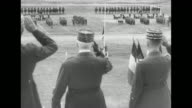 MS open top car carrying Vichy French leader HenriPhilippe Petain drives past with mounted soldier escort soldiers stand at attention in background /...