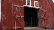Opened doors of red barn w/ two windows above doorway paint somewhat dilapidated old Country countryside farm