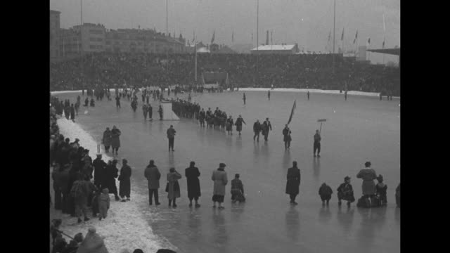 Opening ceremonies on rink in Bislett Stadium delegations of athletes walking carefully on ice / rink with athletes parading and huge crowd in...