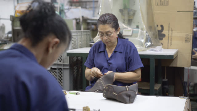 Operator sewing shoe at a shoe factory
