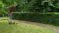 Operator trimming a hedge in a garden.