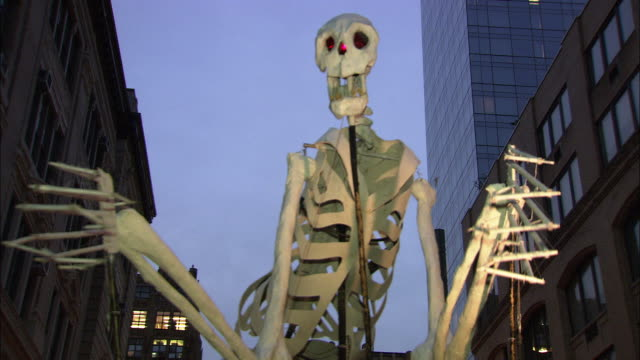 Operators of a giant skeleton puppet get ready for the start of the Halloween parade