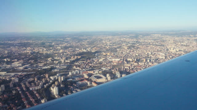 4K | Oporto Portugal seen from above from the window of a plane with the right wing on the foreground.
