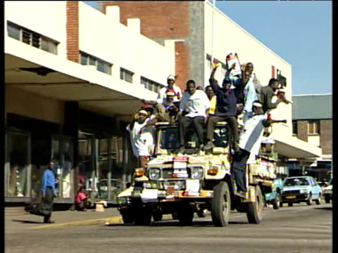 Opposition supporters crowded onto truck driving through streets celebrating winning 57 seats out of 120 27 Jun 00