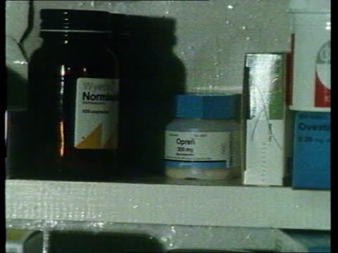 At a Chemist CMS Opren pills bottle taken off shelf MS SIDE female pharmacist taking Opren pills bottle off shelf TCS Opren pills bottle in woman's...