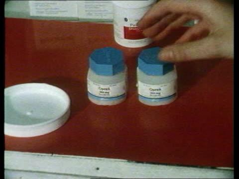 4882 ITN At a Chemist MS SIDE female pharmacist taking Opren pills bottle off shelf TCS Opren pills bottle in woman's hands being put on table CS...