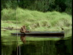 Orang utan paddles boat with her hands, Camp Leakey, Borneo