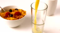 Orange juice pouring into glass at breakfast table