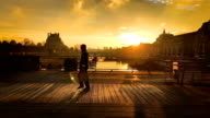 Orange sunrise at Pont Royal bridge People are passing by On the left the museum Le Louvre and on the right the museum Orsay Visible on the...