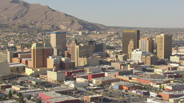 WS AERIAL orbit downtown buildings with mountains in back side / El Paso, Texas, United States