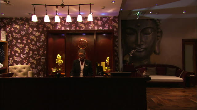 Oriental style hotel lobby, receptionist looks up and smiles, Lough Erne, Northern Ireland