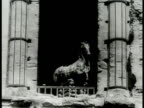 Ornate building statues in courtyard Horse statue by columns Statue of Ancient Roman in robes being moved on dolly Large statue of horse on wooden...