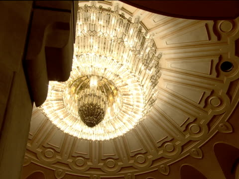 Ornate chandelier hanging off highly decorated theatre ceiling Bucharest