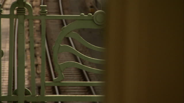 Ornate green railings overlook the tracks at Hietzing U-Bahn station in Vienna, originally built as a private station for the Imperial Court. Available in HD.