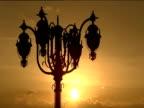 Ornate street light silhouetted in golden sunset Bucharest
