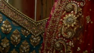 Ornately embroidered and beaded dresses hang in a shop in Mumbai.