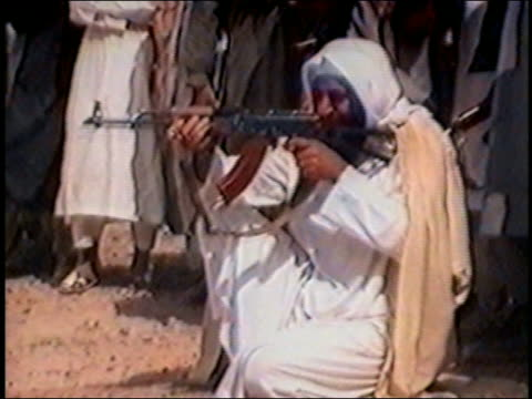 Osama bin Laden kneeling / aiming and firing rifle / AUDIO
