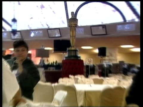 SHOWBIZ / Oscars preview ITN INT Workers ironing tablecloths PULL OUT Tables being prepared