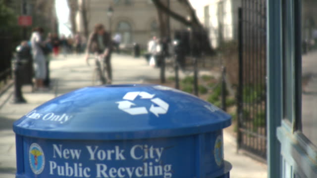 CU Out of focus man throwing cup away into recycling bin, New York City, New York, USA