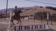 Outdoor jumping ring, medium close on horse and rider, rider Haley clears two jumps on Allie.