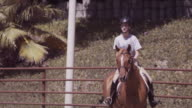 Outdoor jumping ring, medium close-up, Haley rides into position
