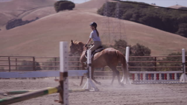Outdoor jumping ring, rider Haley canters horse, then breaks towards two jumps and clears them, slow motion