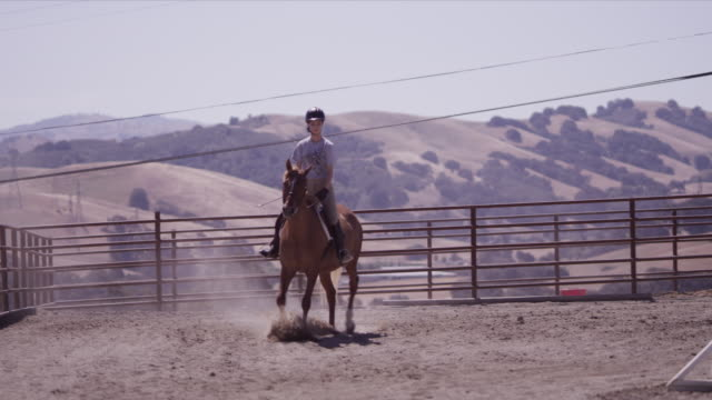 Outdoor jumping ring, rider Haley canters horse toward camera, slow motion