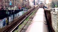 Outdoor MTA tracks partial city buildings BG 1 train passing through bottom to top frame NYC