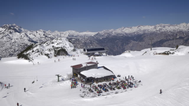 AERIAL over busy ski lifts on top of ski resort