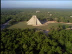 AERIAL over Chichen Itza pyramid temple ruins surrounded by forest / Yucatan, Mexico