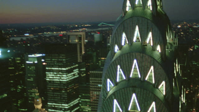 AERIAL over Chrysler Building at dusk / Empire State Building in background / NYC