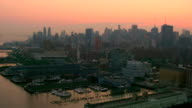 WIDE AERIAL POV over Hudson River waterfront and piers toward Midtown Manhattan at twilight