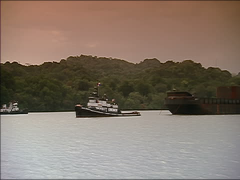 WS, ZOOM OUT, PAN RIGHT over Miraflores Lake as several tug boats surround a small barge travelling over the lake with tree covered land in B/G and rose colored sky above.