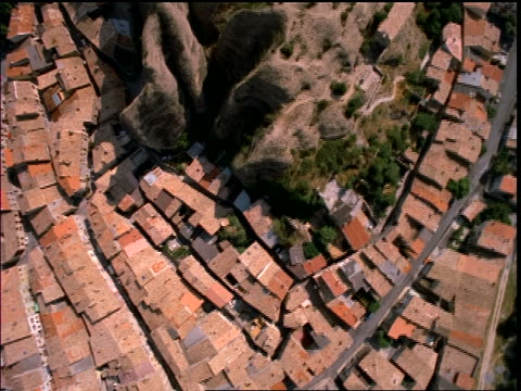 AERIAL over rooftops of village + rock formations (Les Penitents) / Provence, France