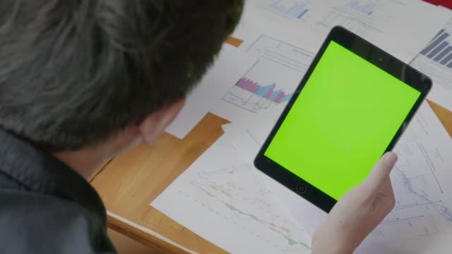 Over de schouder schot van zakenman met behulp van digitale tablet, groen scherm
