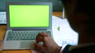 Over shoulder shot of Businessman using laptop with a green screen, 4k(UHD)