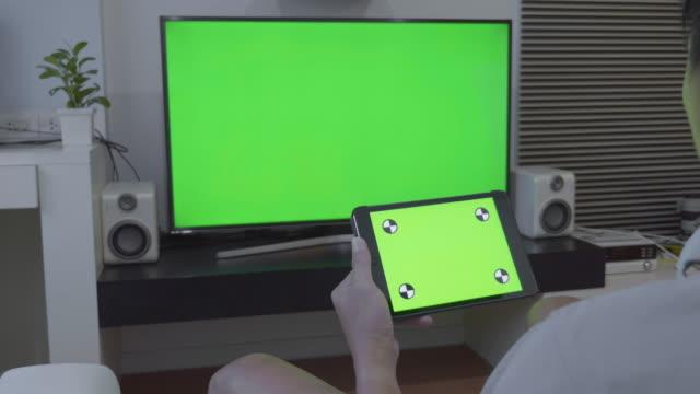 Över axeln skott av digitala tablett och TV, grön skärm