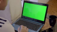 Over shoulder shot of laptop with a green screen